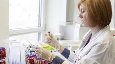 Mitarbeiterin des LSL mit Blutprobe